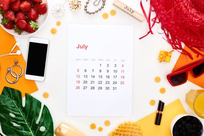 july 2020 calendar page, wooden block with july inscription, smartphone, sunglasses, orange juice, fresh strawberry, waffles, cosmetics, earphones, lollipops isolated on white - stock photo