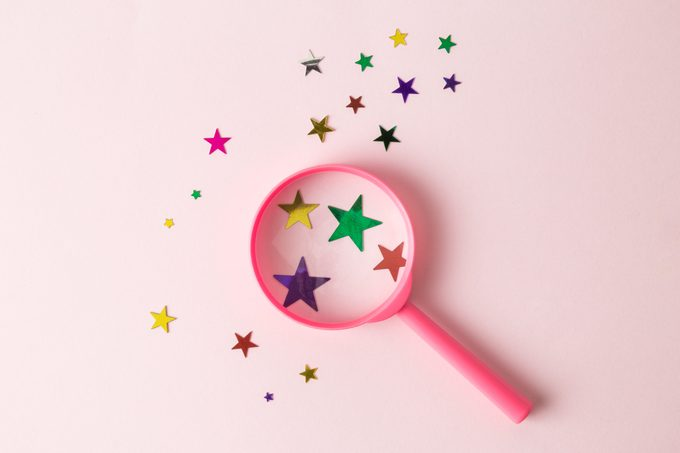 Top view of magnifier and different sizes multicolored stars on pastel rose background abstract.
