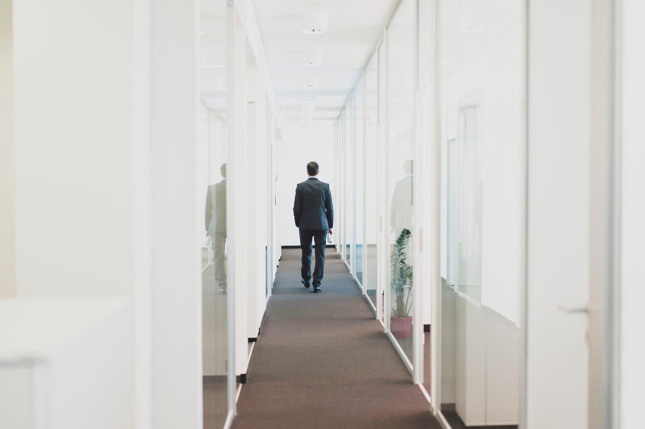 Rear view of businessman walking down office corridor