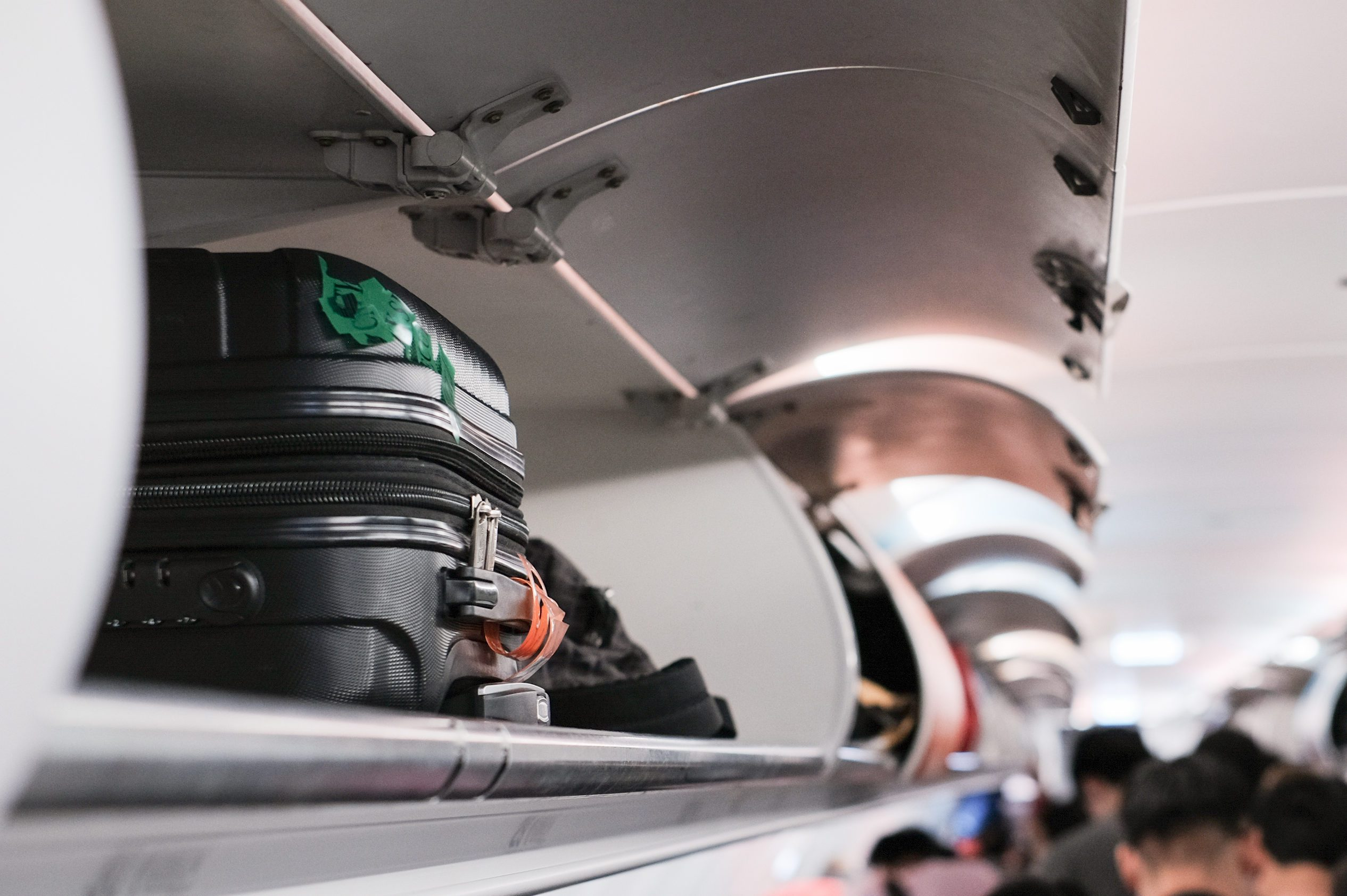 overhead locker on airplane,Passenger put cabin bag cabin on the top shelf. Travel concept
