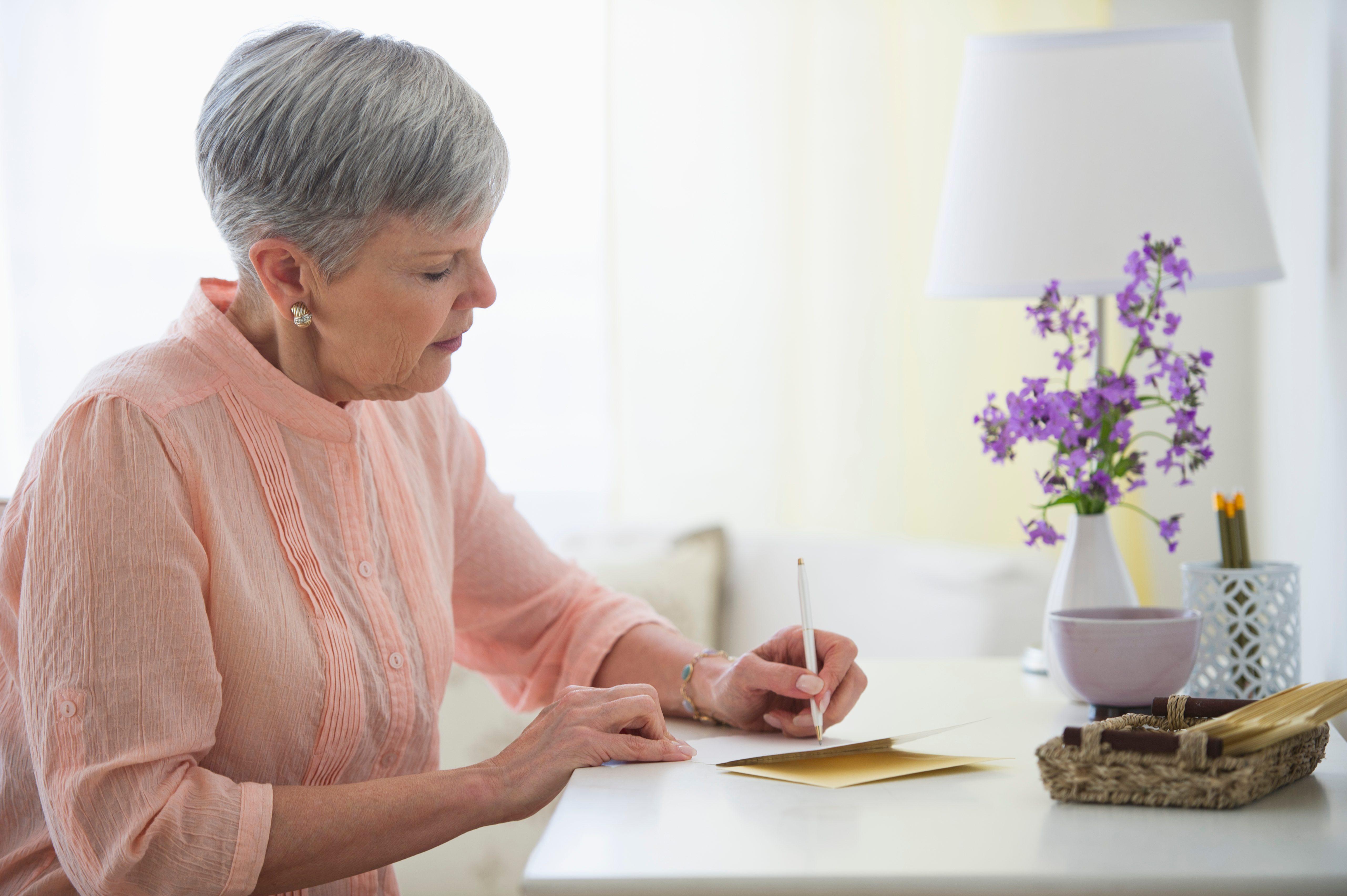 USA, New Jersey, Jersey City, Senior woman writing letter