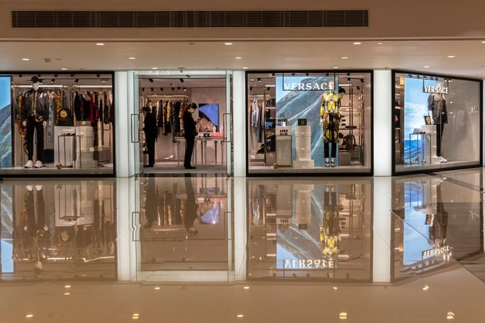 A masked shop keepers of the luxury brand Versace inside the...