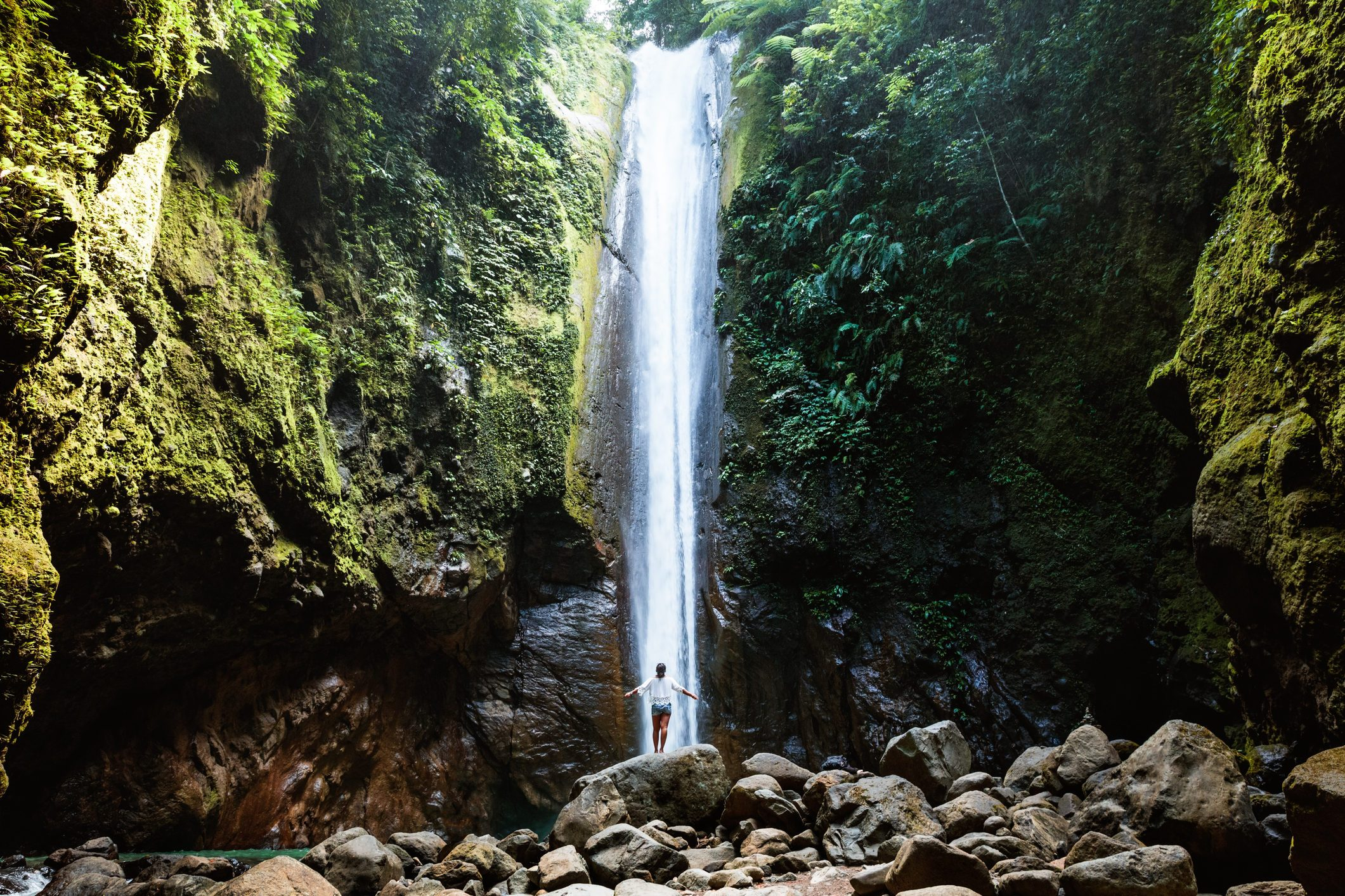 Woman under tall waterfall, Negros, Philippines