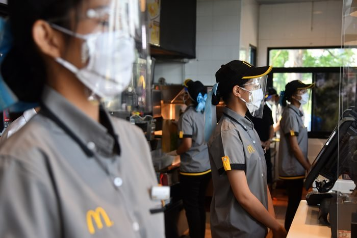 An employee of McDonald's wearing a protective mask and a...