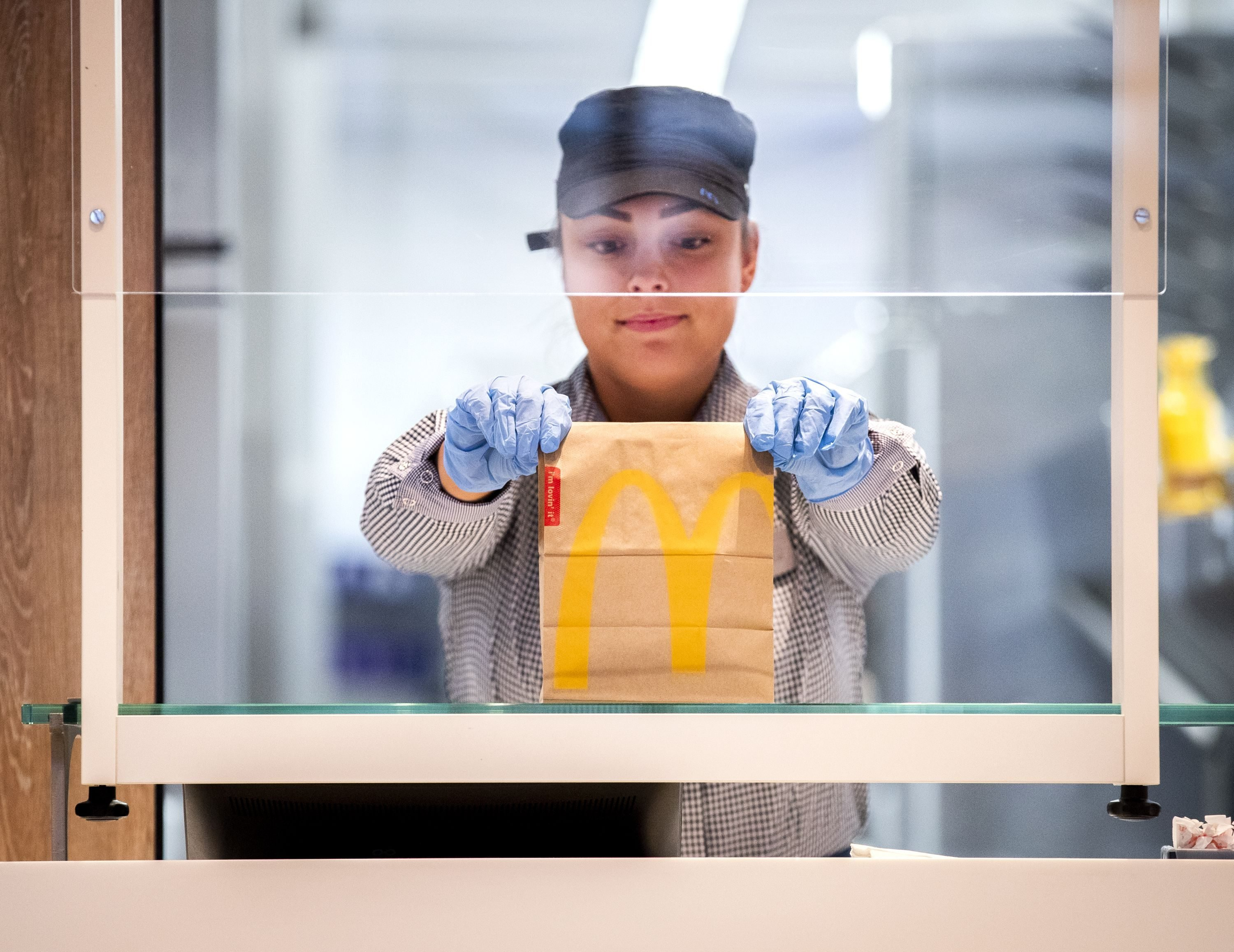 A McDonalds' employee holds up a food package at a test location in a restaurant at The GelreDome Arnhem, The Netherlands on May 1, 2020, as part of measures to attempt to stop the spread of COVID-19 (novel coronavirus). - In this restaurant prototype, the fast food chain shows what seated catering in the 1.5 meter economy could look like. There are two variants: Take Out Plus and Dine In. (Photo by Remko DE WAAL / ANP / AFP) / Netherlands OUT (Photo by REMKO DE WAAL/ANP/AFP via Getty Images)