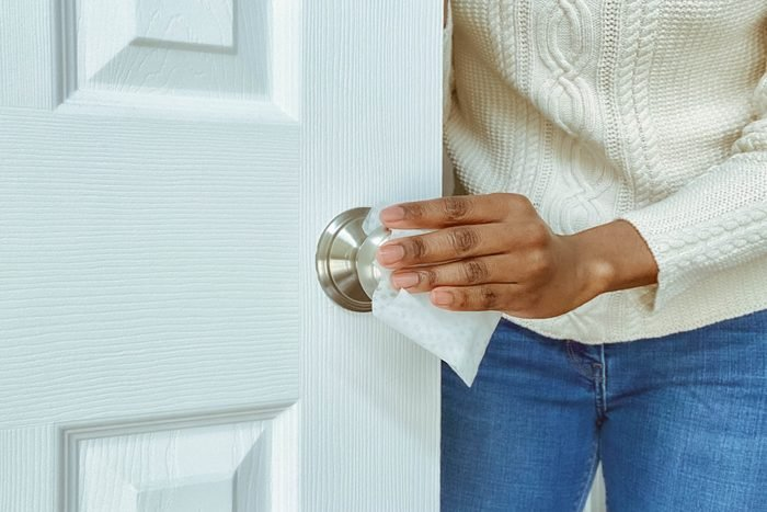 Woman Cleans Interior Doorknob Using Disinfectant Wipe