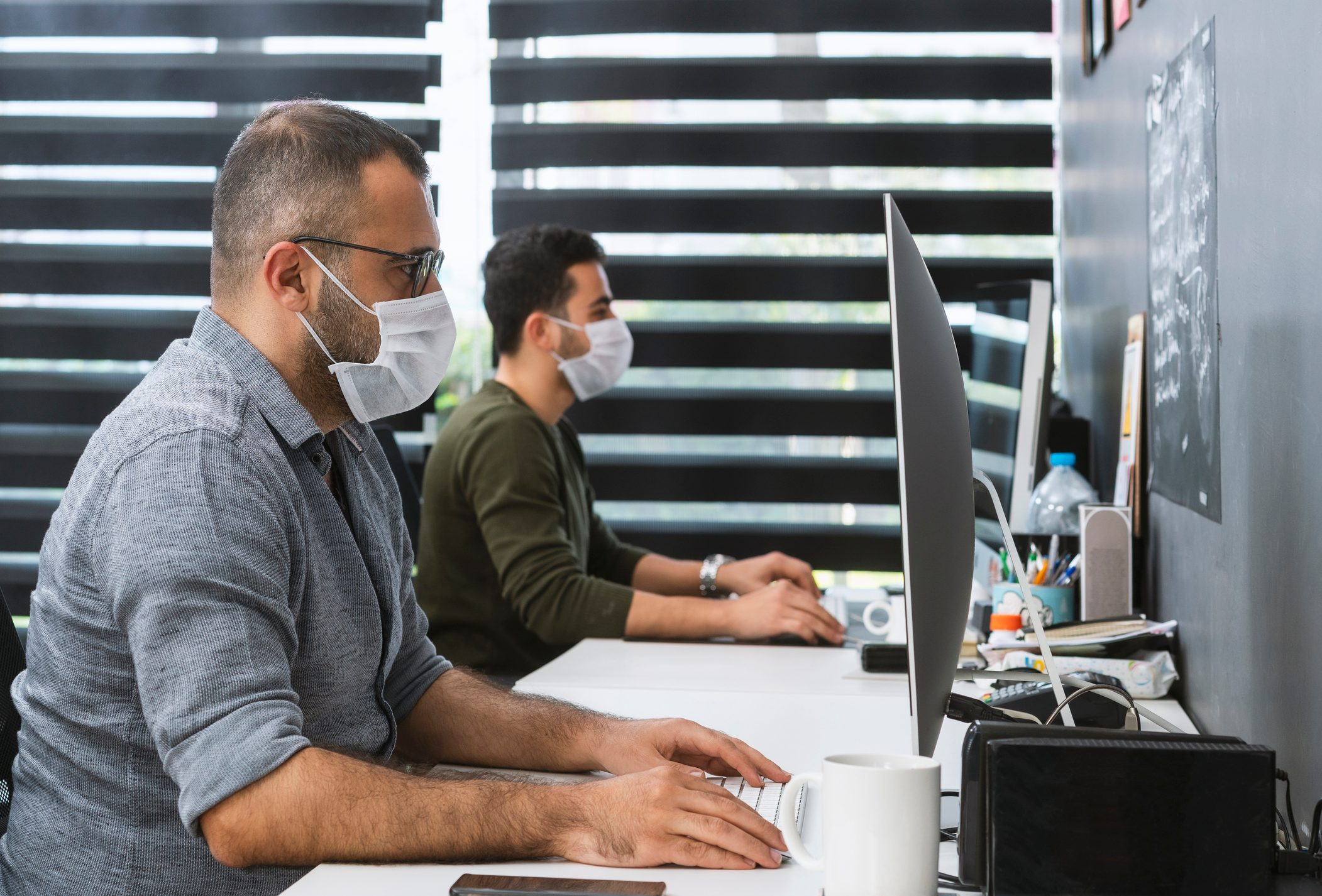 Two businessmen with protective face masks are working in the office