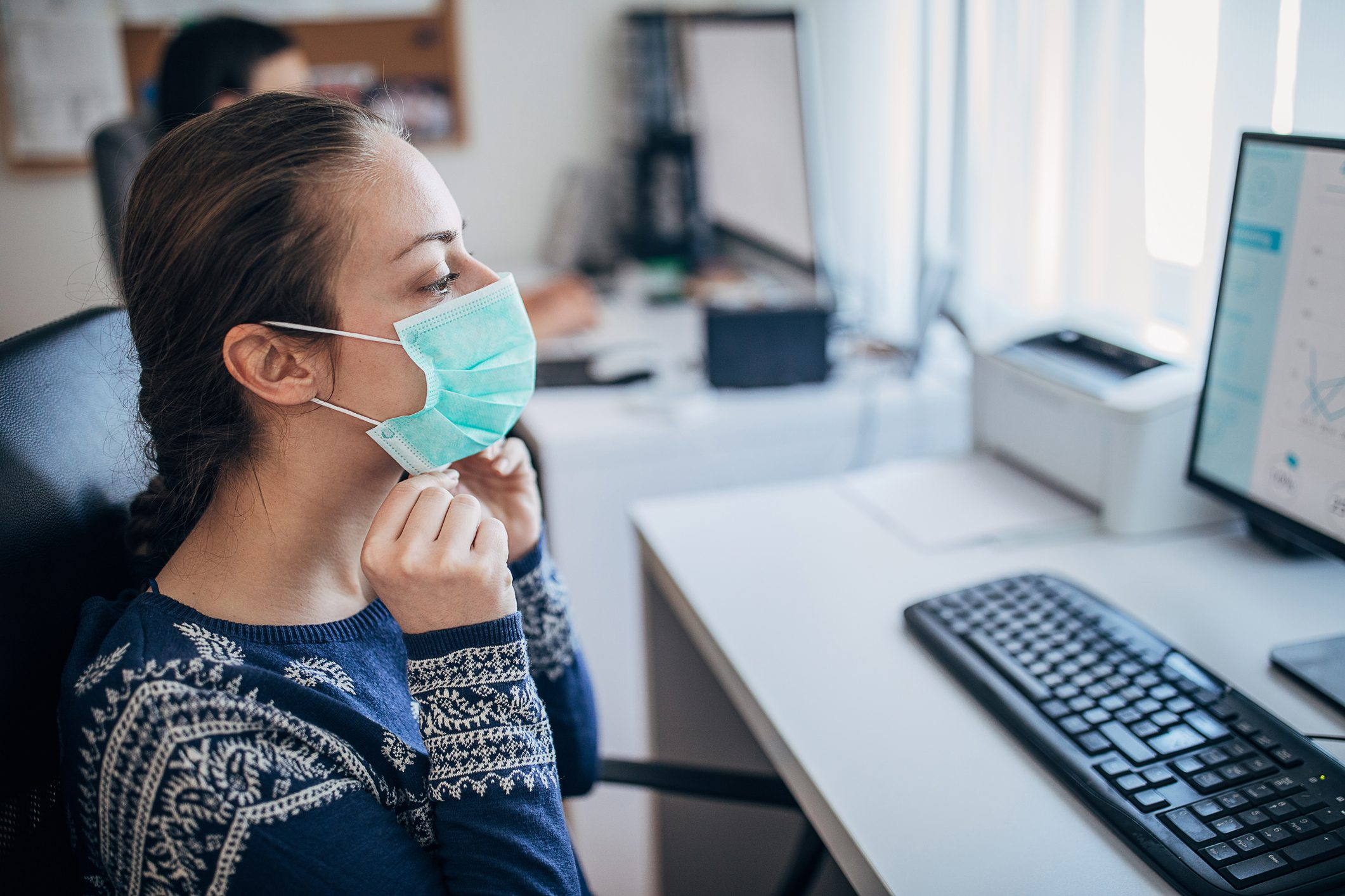 Young woman in the office putting on the protective mask, to prevent coronavirus from spreading