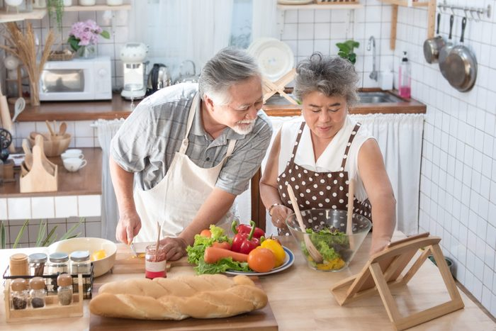 Looking for new recipes. Asian senior elderly couple using digital tablet at kitchen, enjoying cooking together at home in leisure time.