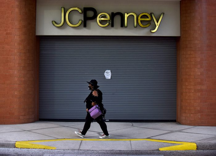 A woman walks by a JC Penney store that was temporarily...