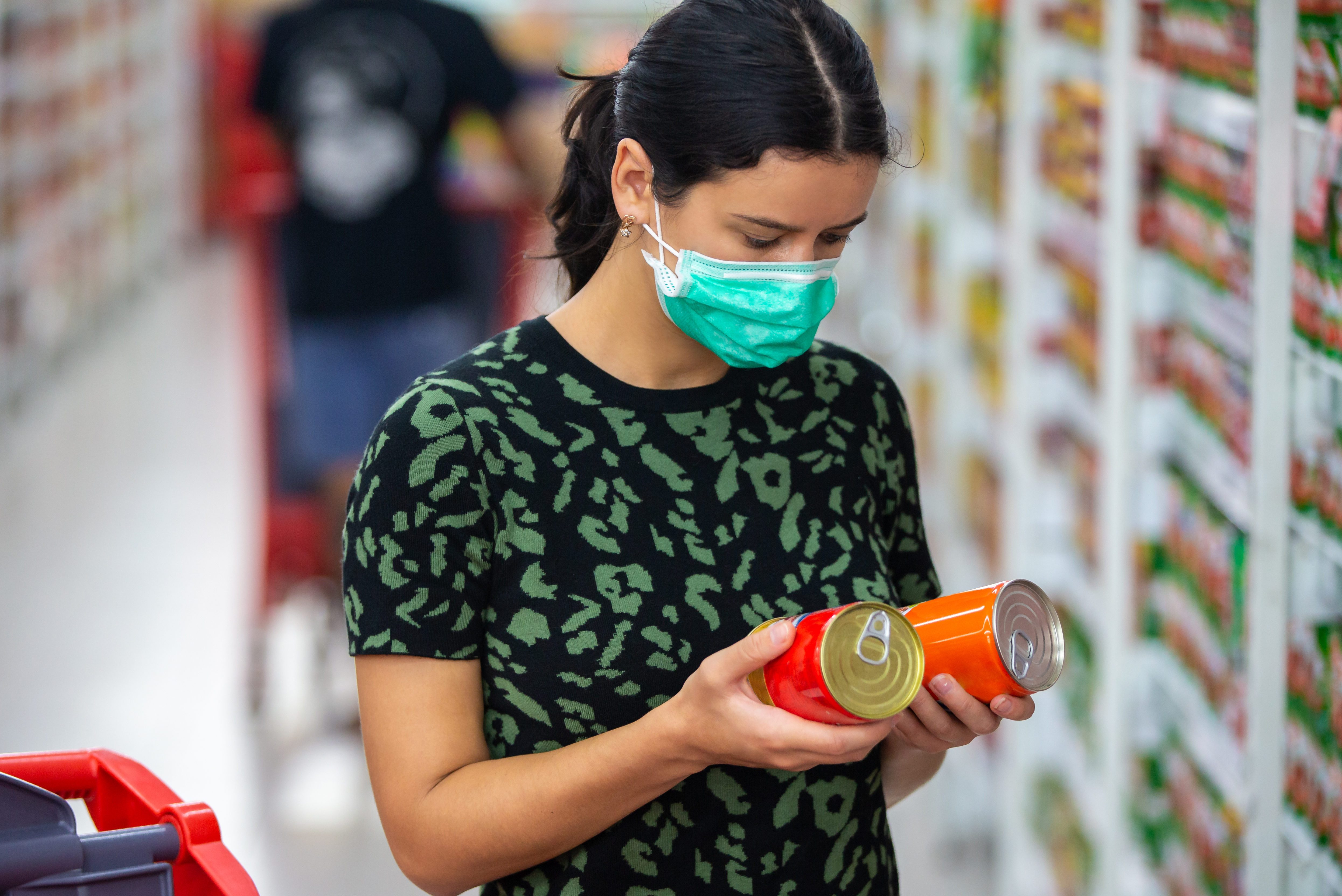 Alarmed female wears medical mask against coronavirus while grocery shopping in supermarket or store- health, safety and pandemic concept - young woman stockpiling food in fear of covid-19
