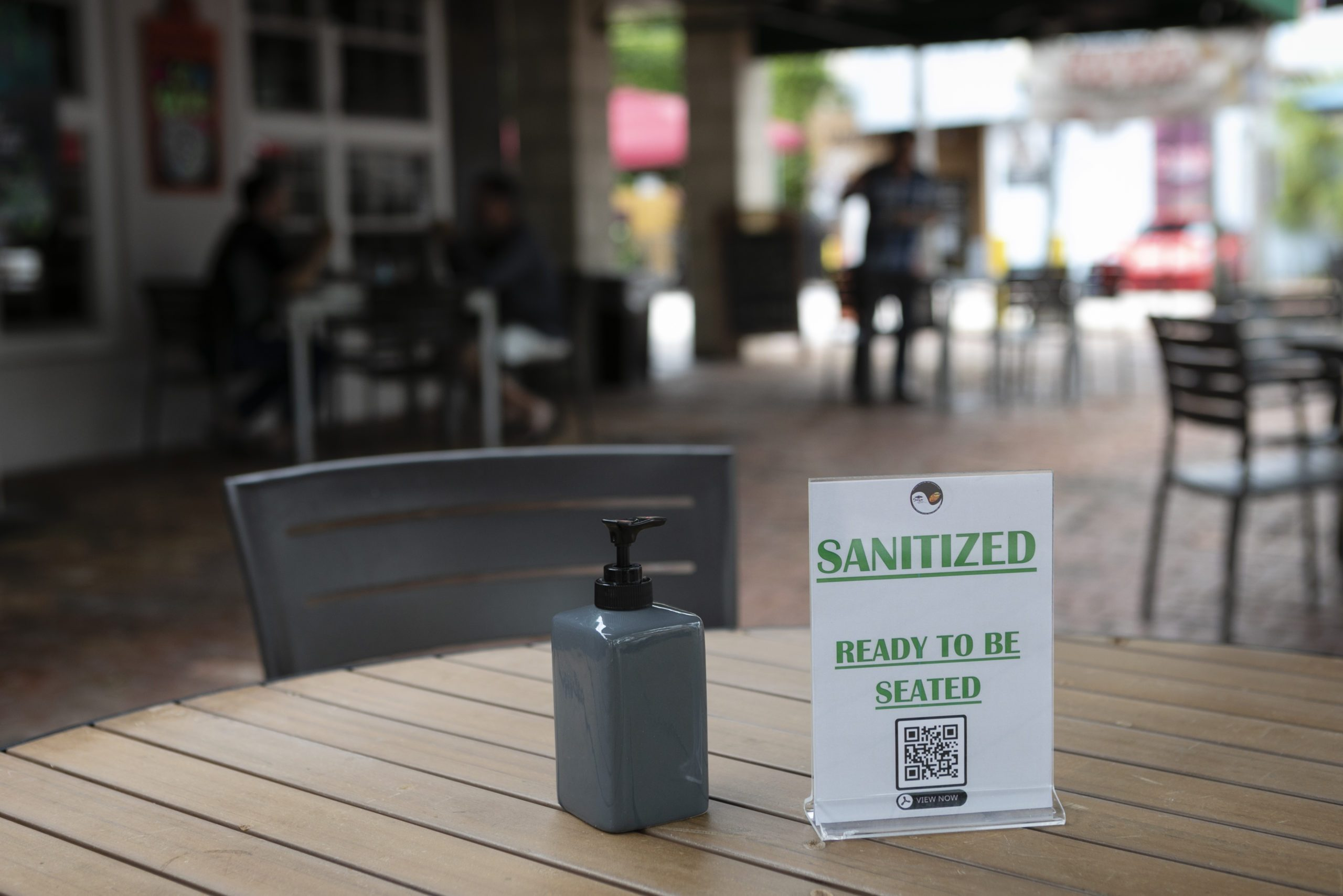 "A sign reading ""Sanitized, ready to be seated"" is seen on a table in a restaurant terrace"