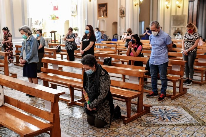 Believers wearing protective masks are social distancing in...