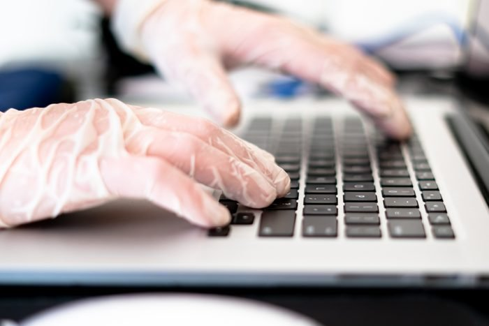 Close up of hands typing on laptop with surgical gloves