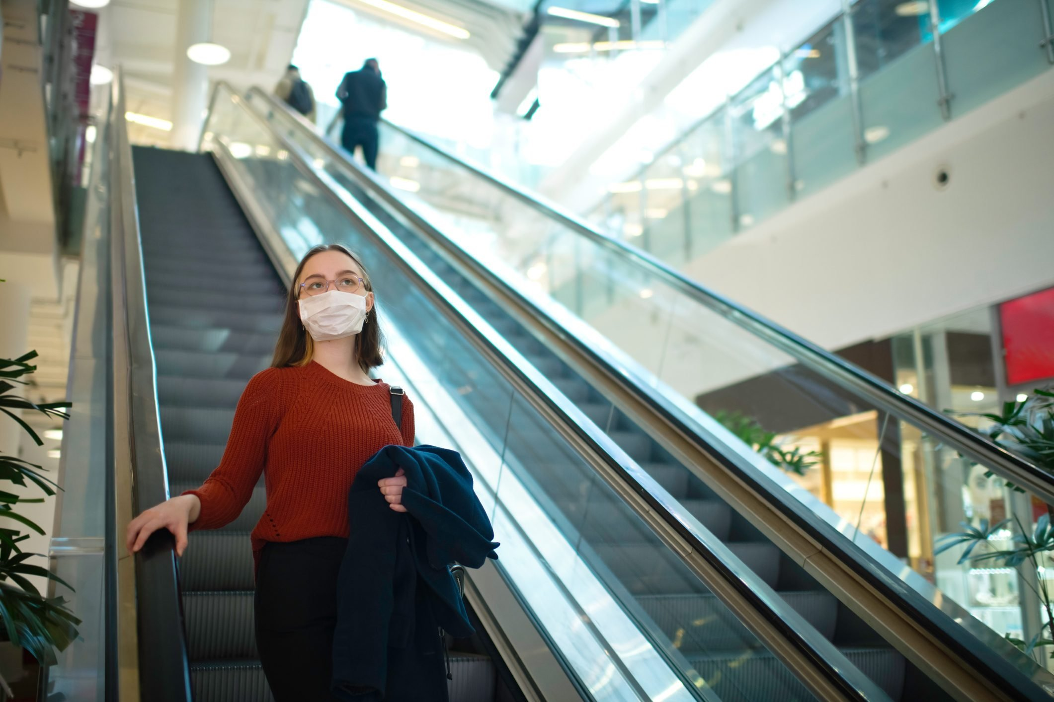 Young girl on an escalator in shopping mall wearing medical mask to protect herself against virus or pollution