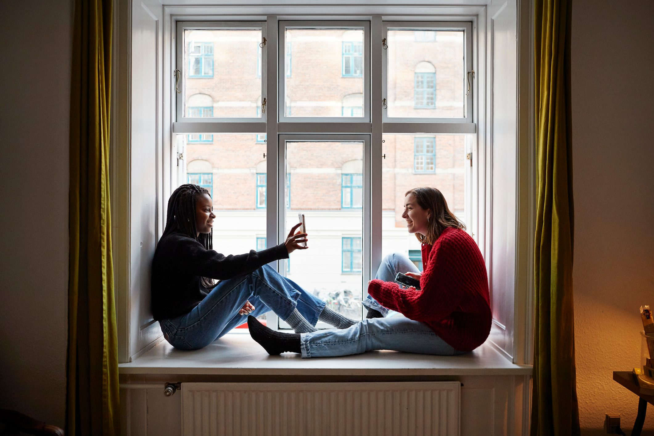 Young female roommates using smart phones at apartment window