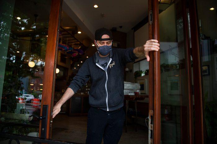 masked man opens restaurant doors