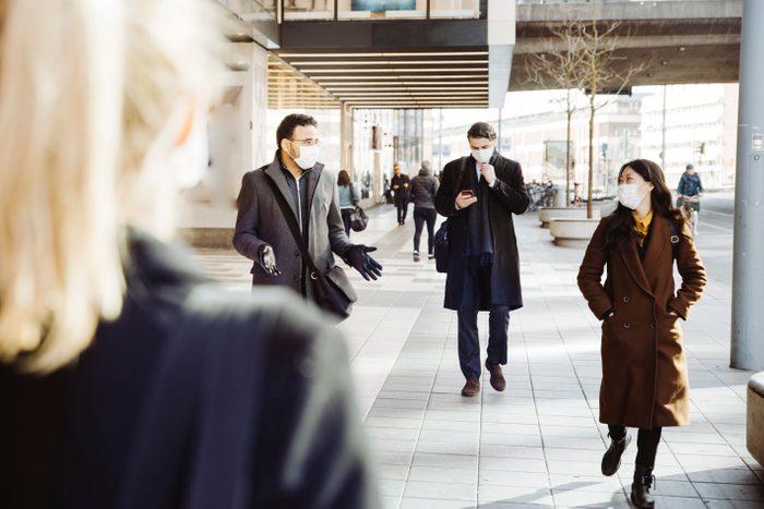 Business people wearing face mask walking in street
