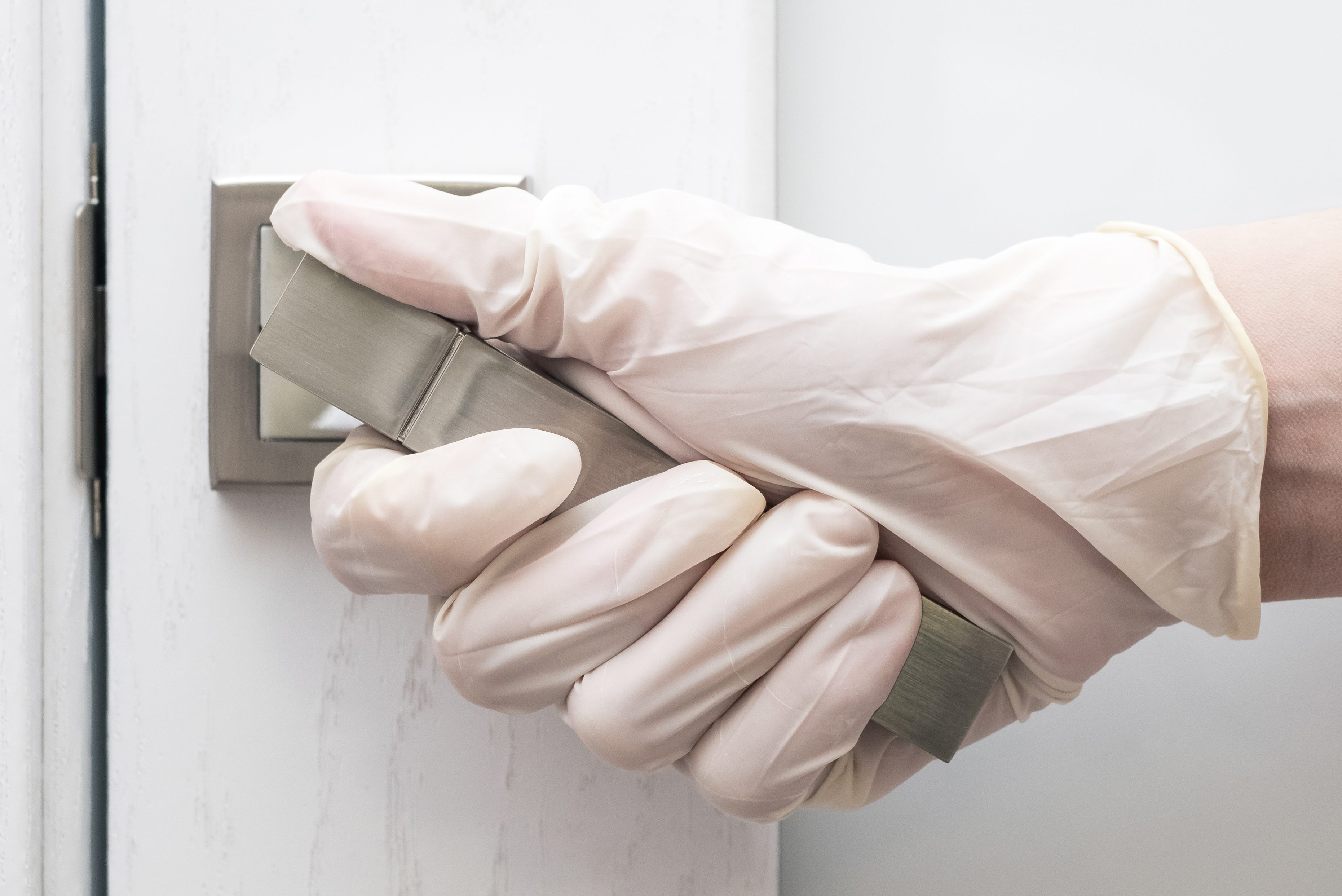 Hand in a rubber glove holding the door handle of the front door, close-up. Concept of protection against coronavirus and flu. Door handle, as a collection of microbes and bacteria, a virus carrier
