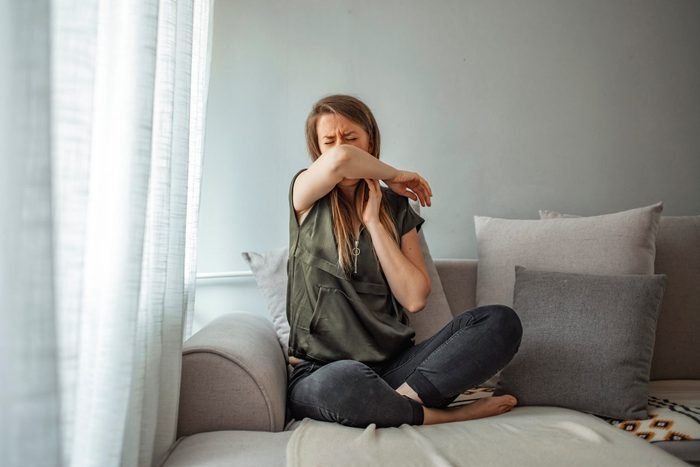 Woman cough in arm prevention.