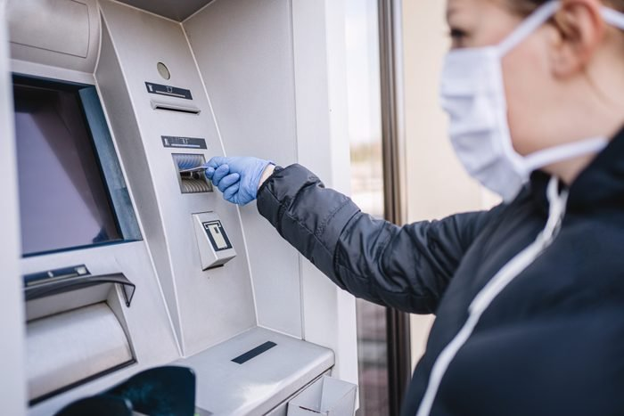 Woman with gloves and a face mask on a bank ATM using a credit card during a coronavirus pandemic