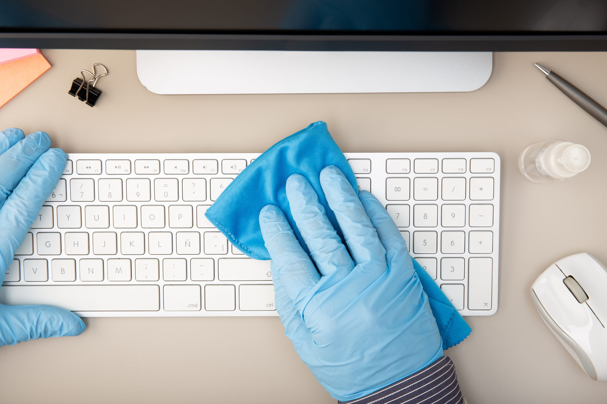 Cropped Hands Wearing Gloves Cleaning Keyboard On Desk