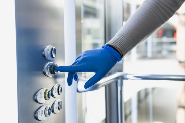 Hand in a rubber glove presses the elevator or lift button.