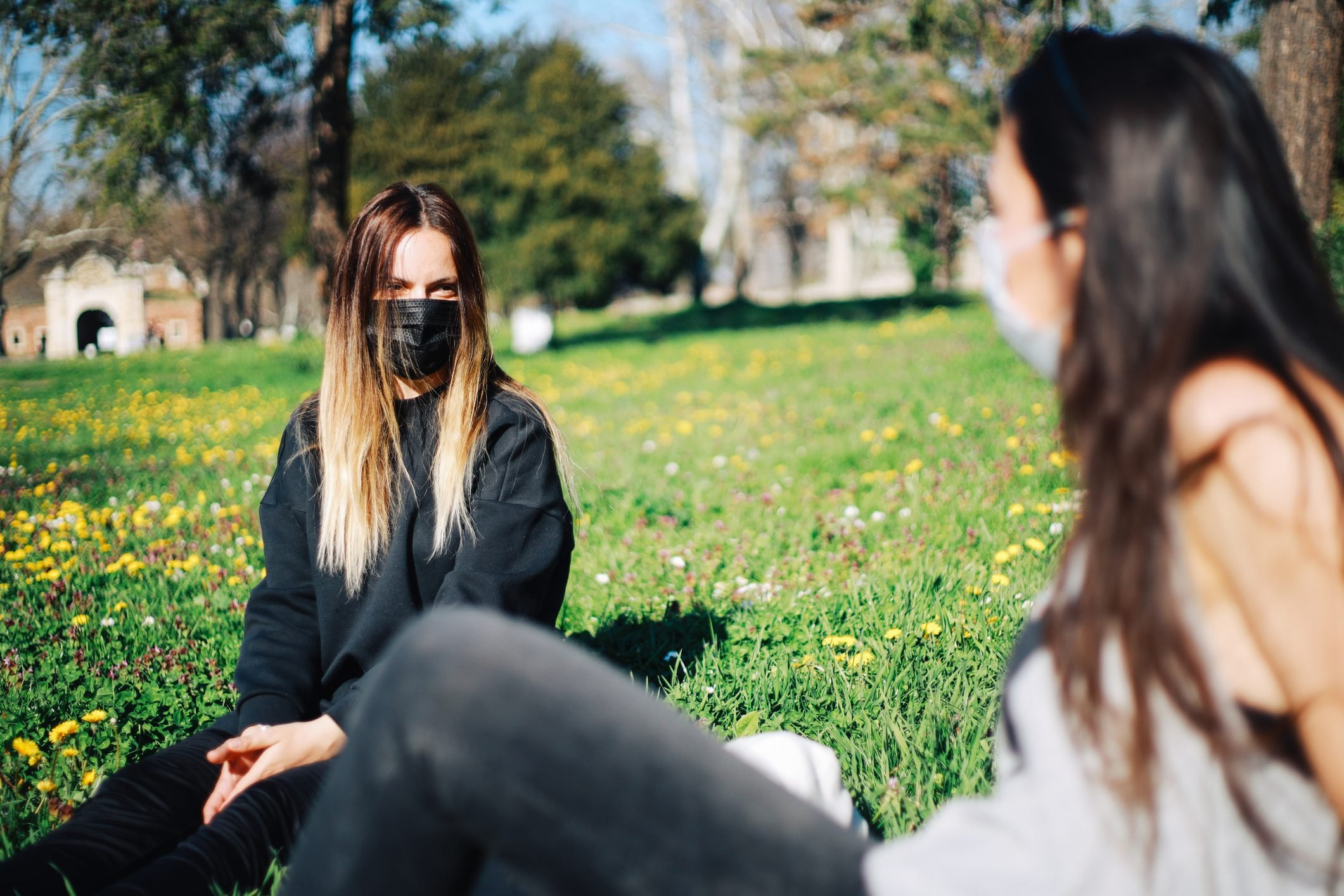 Two girls with masks in the park during pandemic