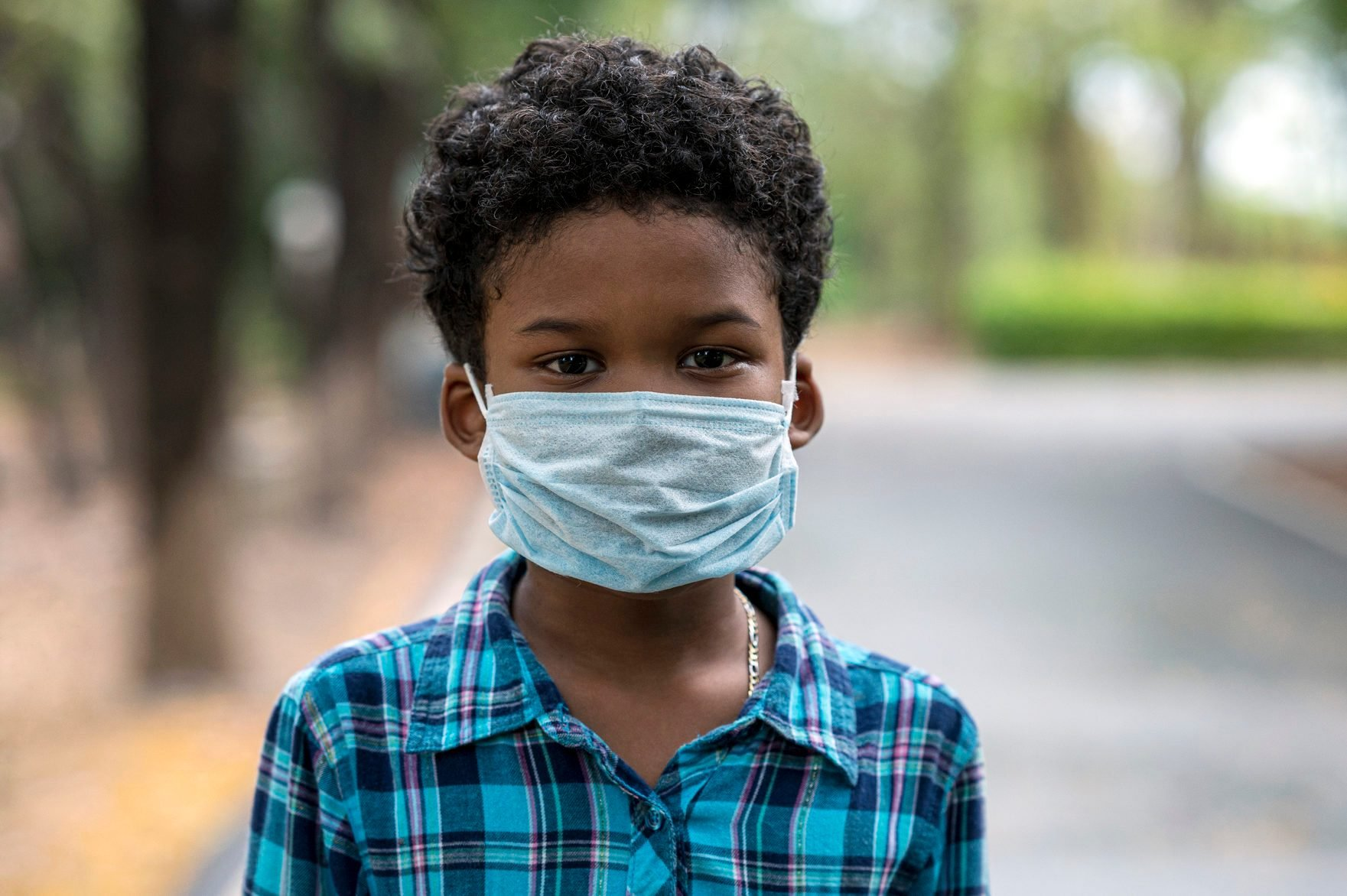 Boys wear face mask in the public park during COVID-19 pandemic. New normal living after COVID-19 pandemic.