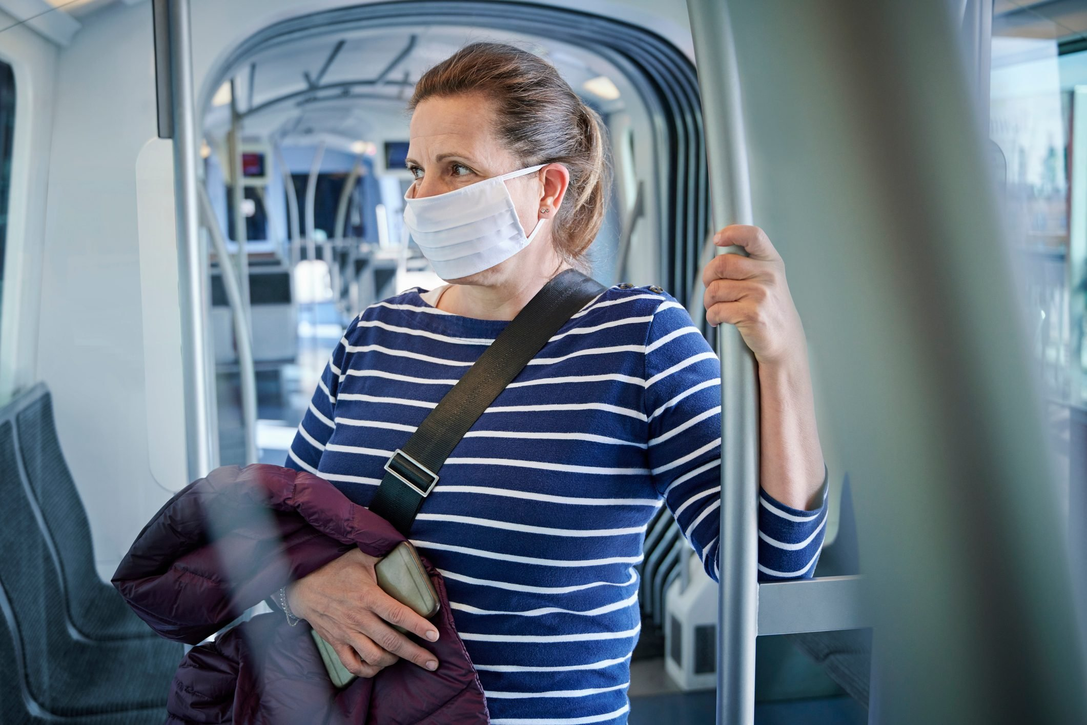 Mature woman wearing protective mask on train