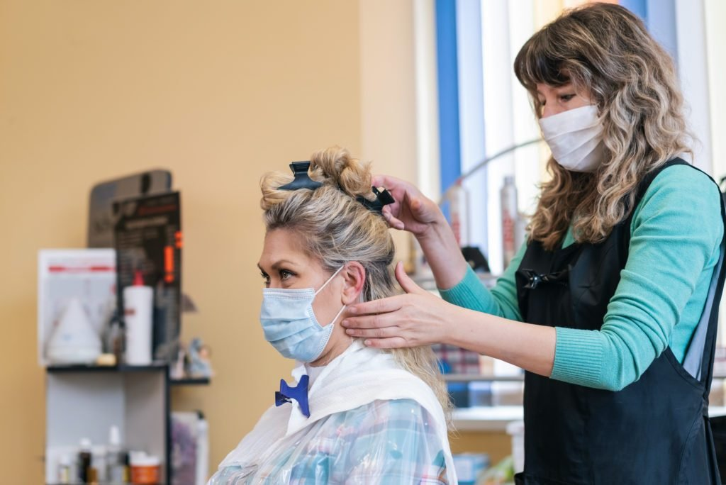 Hairdresser makes beautiful hairstyle, during COVID-19