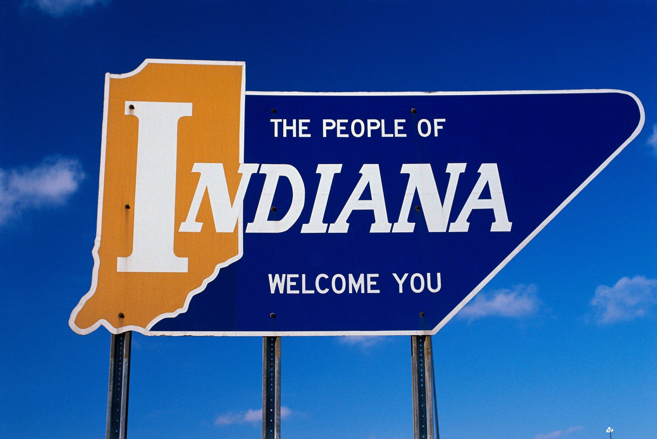 Road sign that says the people of Indiana welcome you