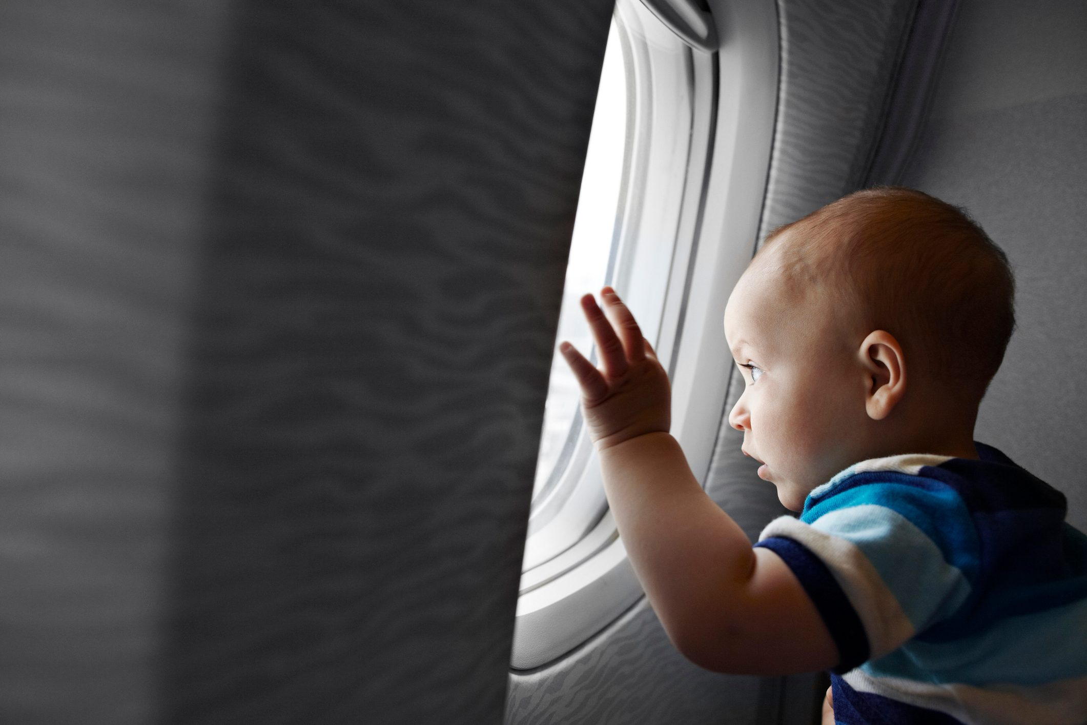 Baby boy looking fascinated out of airplane window
