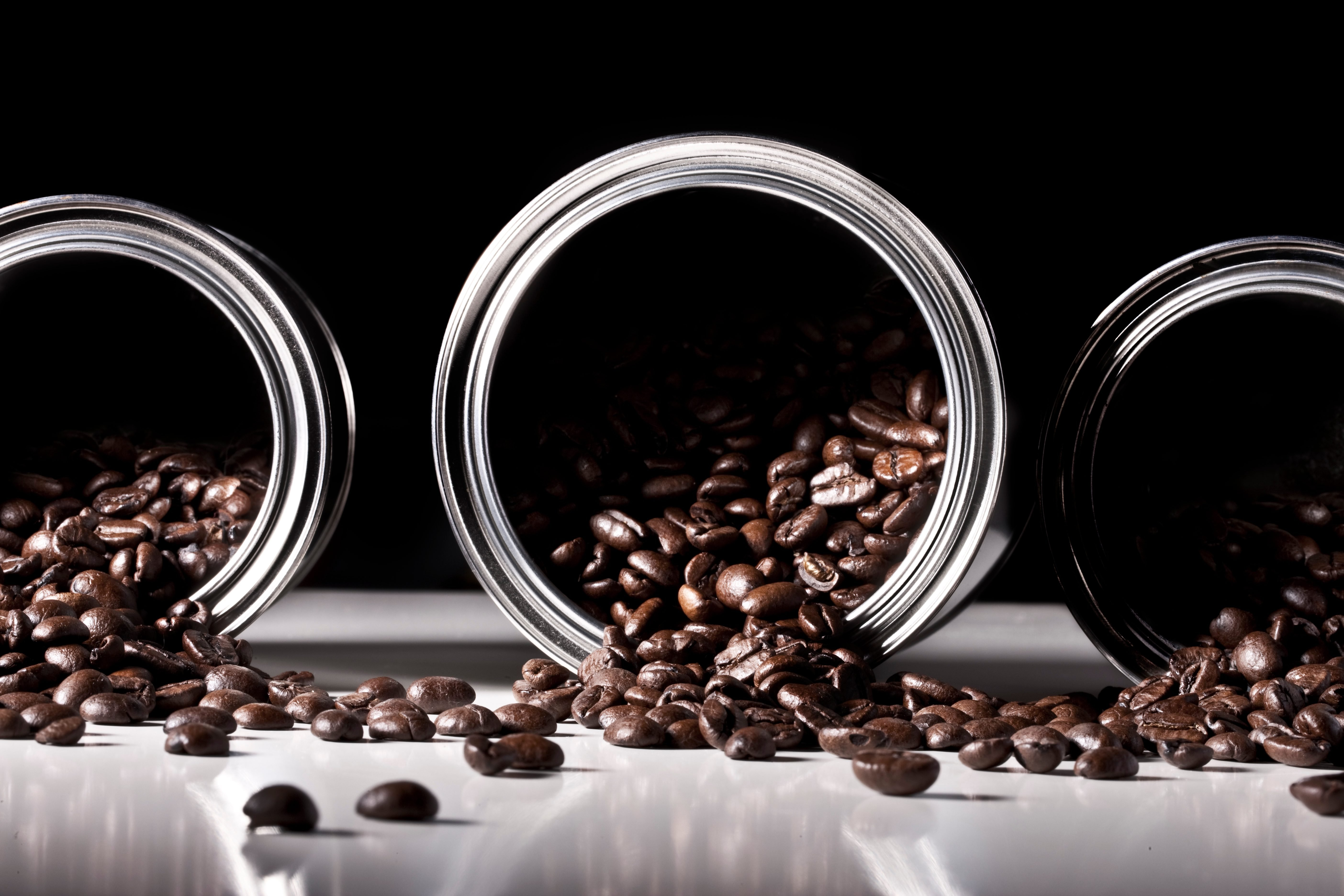 Studio shot of coffee beans spilling from tins