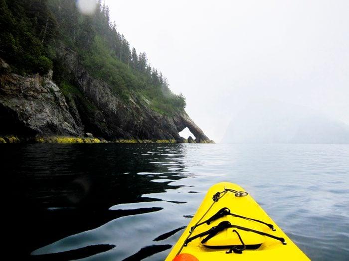 A pair of sea kayakers paddles during a grey Alaska summer day on the Pacific Ocean along Fox Island, Alaska.
