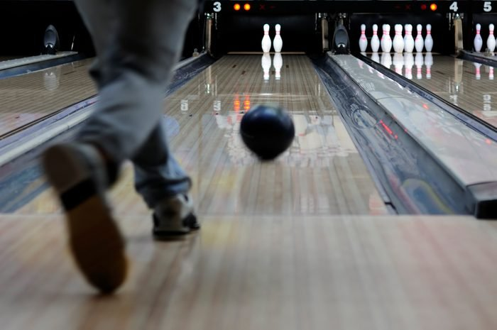 Person Throwing a Bowling Ball Down the Alley Lanes