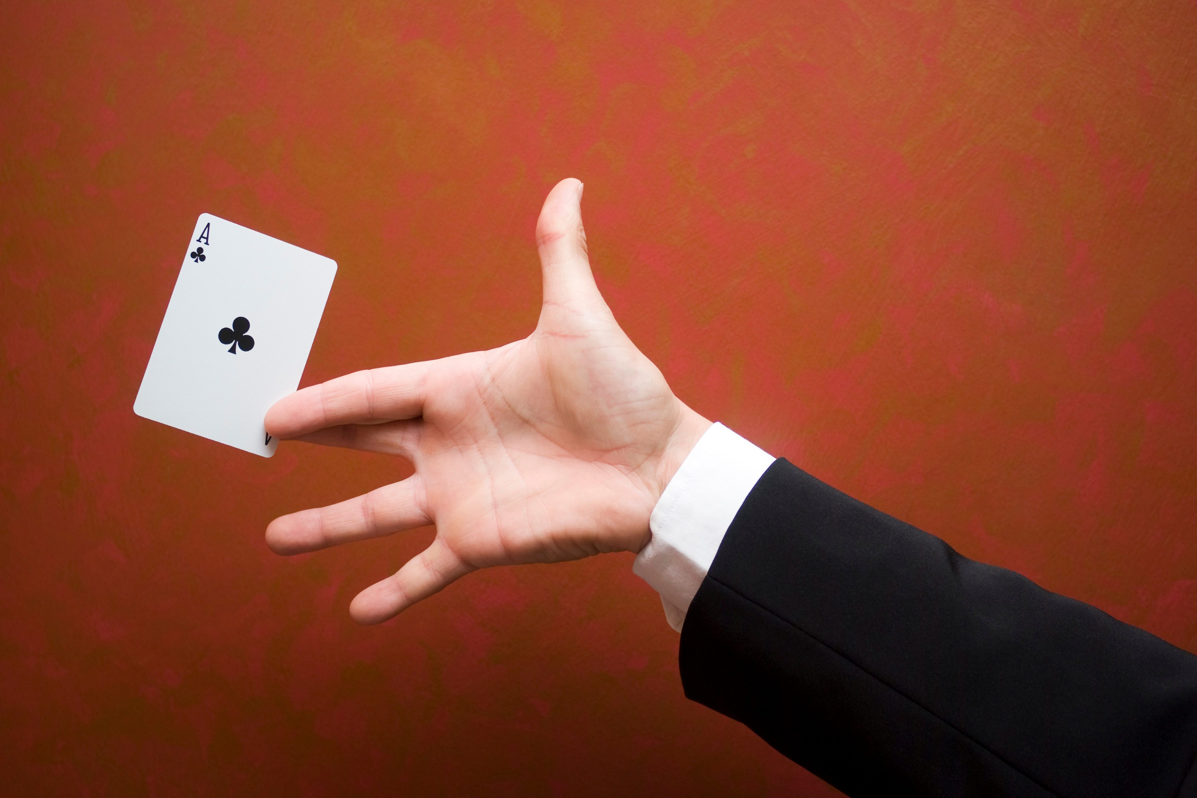 Close-up of magician performing trick with ace card