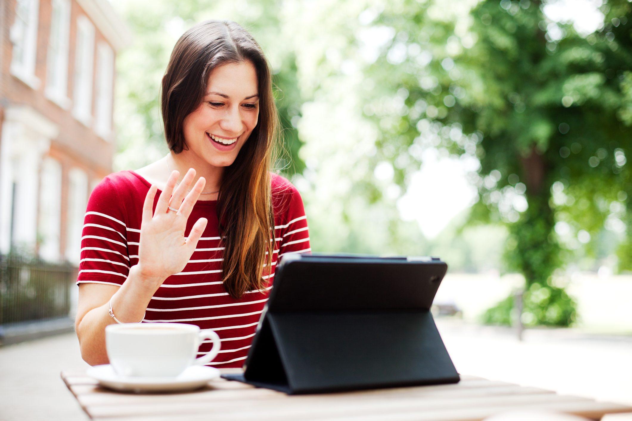 Woman waving at digital tablet.