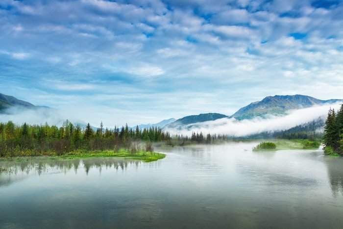 Lake and mountain landscape with early-morning fog