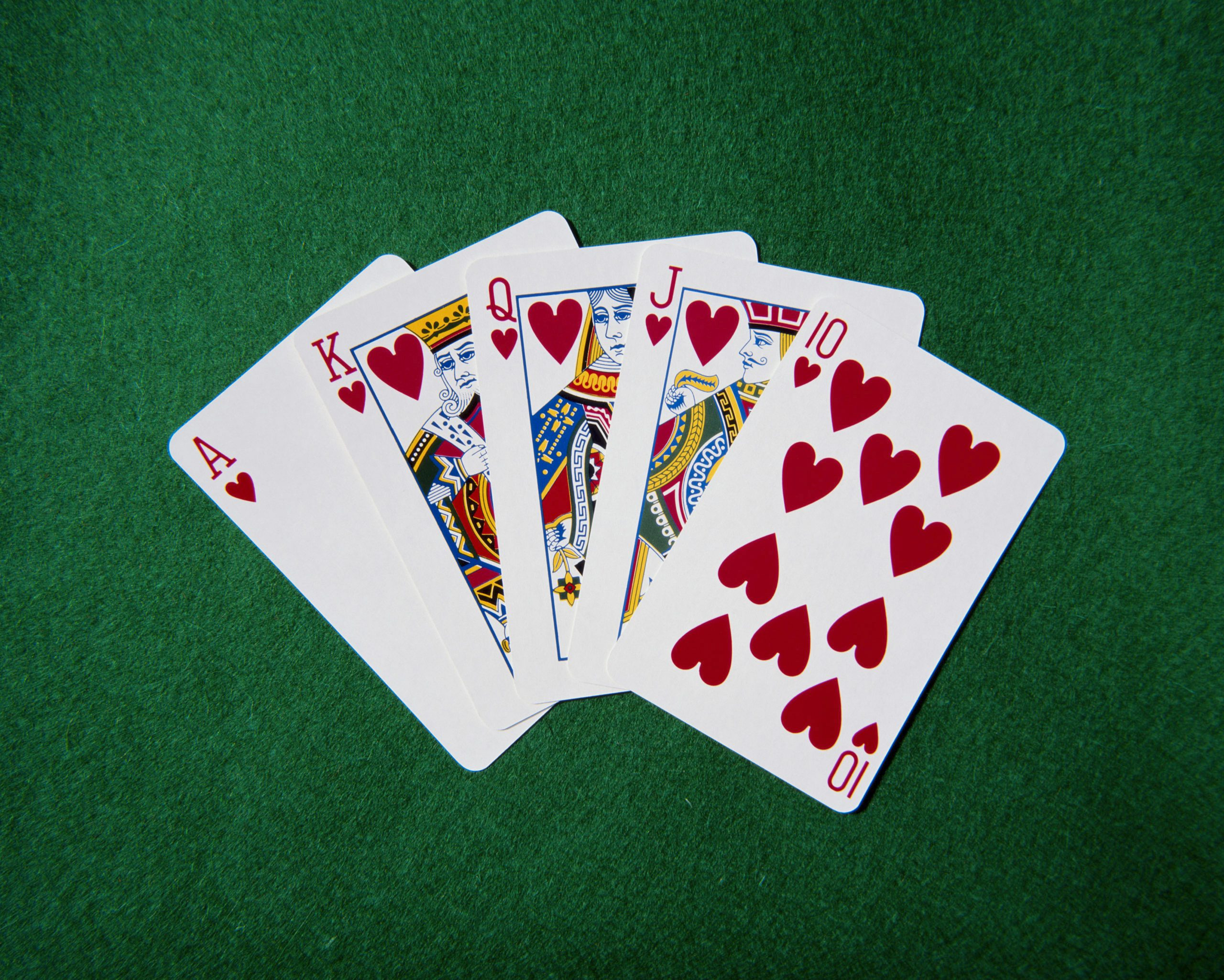 Royal flush hand of cards, hearts suit, on playing baize, close-up