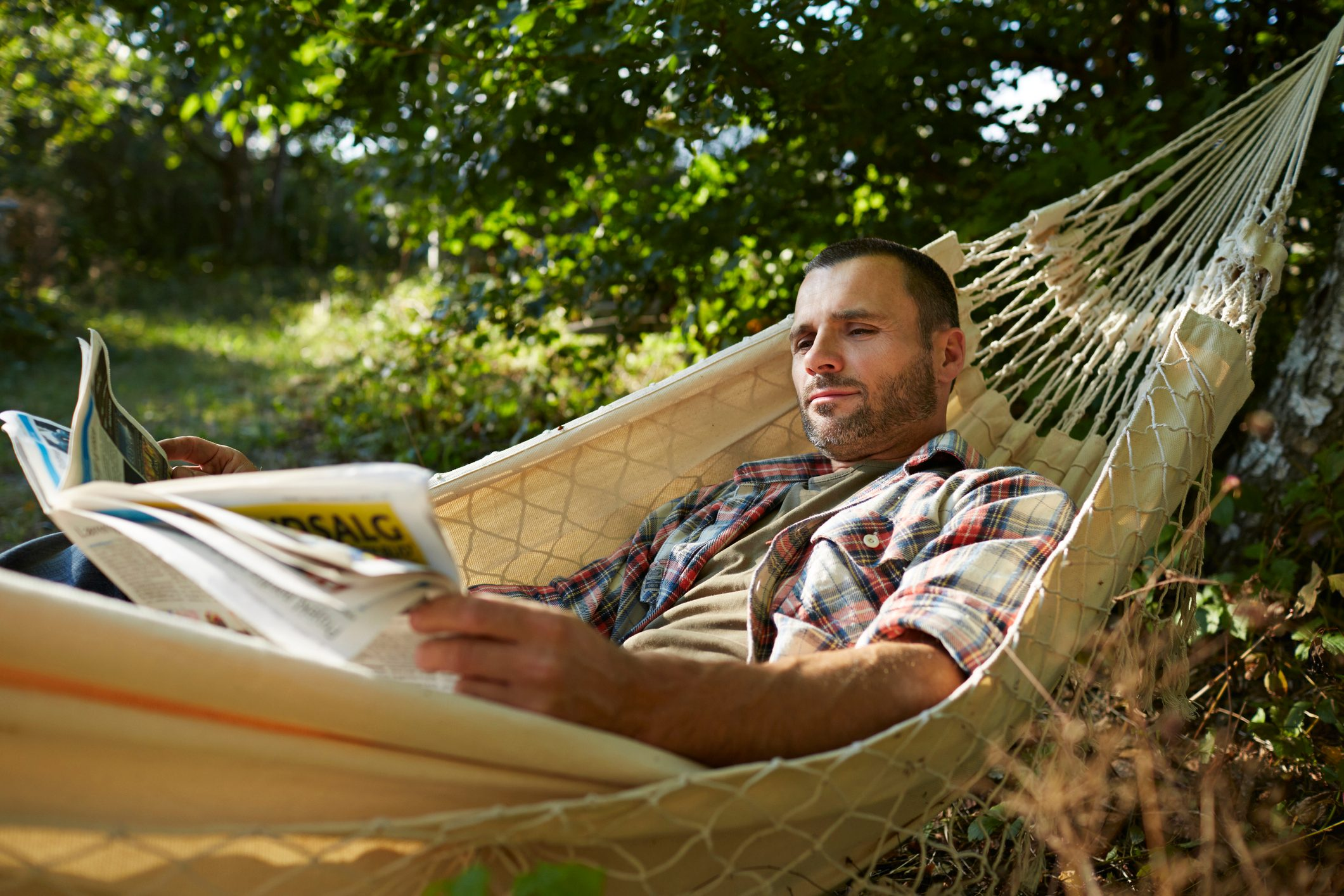 Man lies in hammock reading the paper