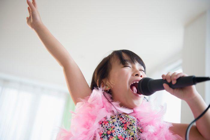 Filipino girl singing karaoke in living room