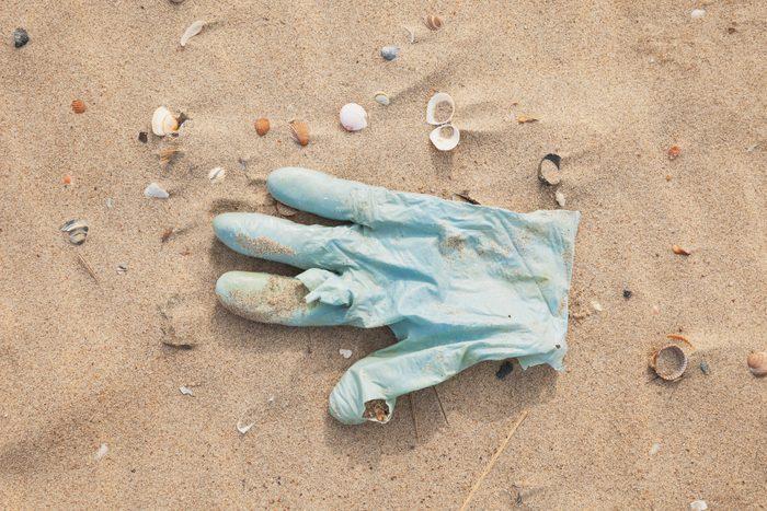 Belgium, rubber glove lying on sandy beach at North Sea coast
