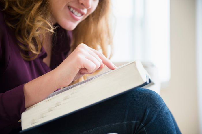 USA, New Jersey, Young woman reading book