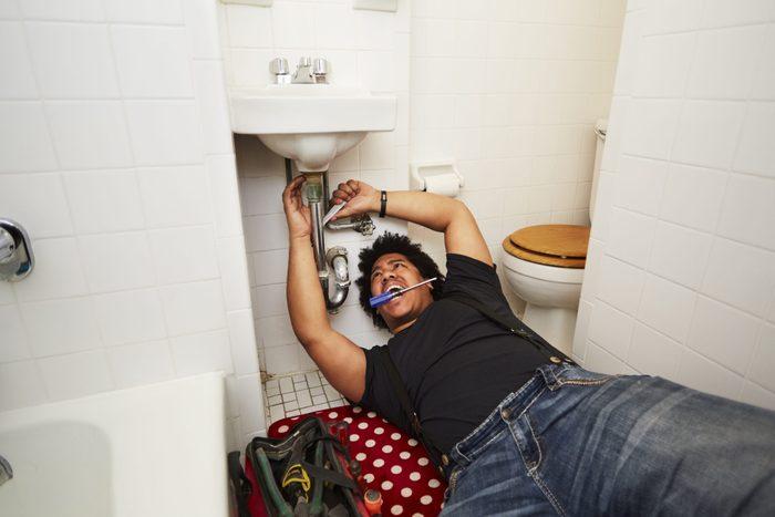 Mixed race man fixing sink plumbing