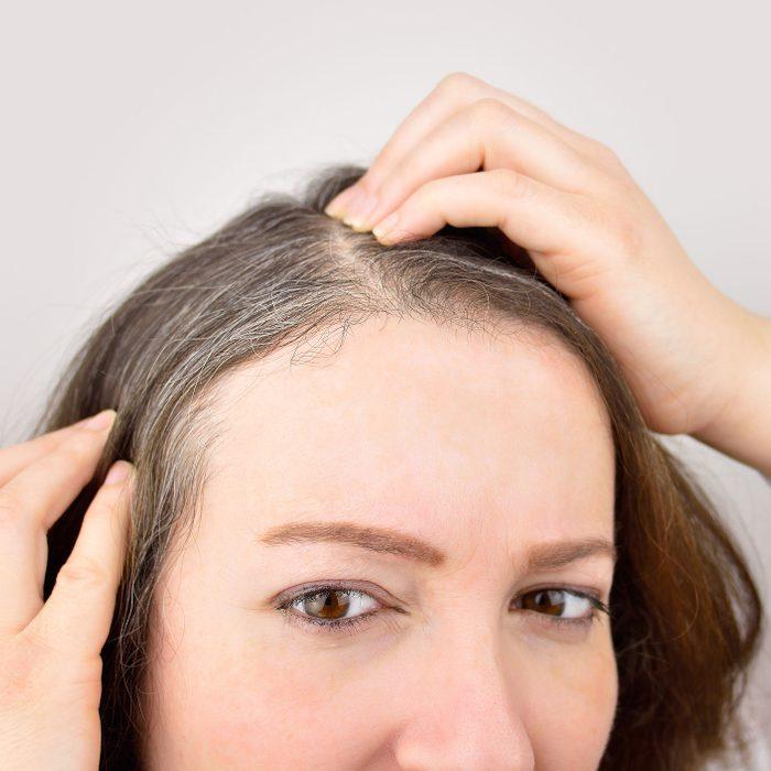 woman examining her grey hair roots