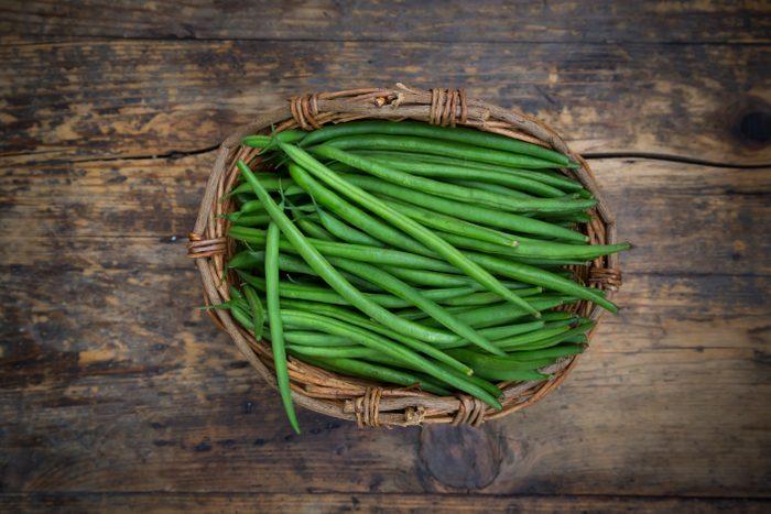 Wickerbasket of green beans on dark wood