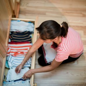 overhead view of woman organizing a drawer at home