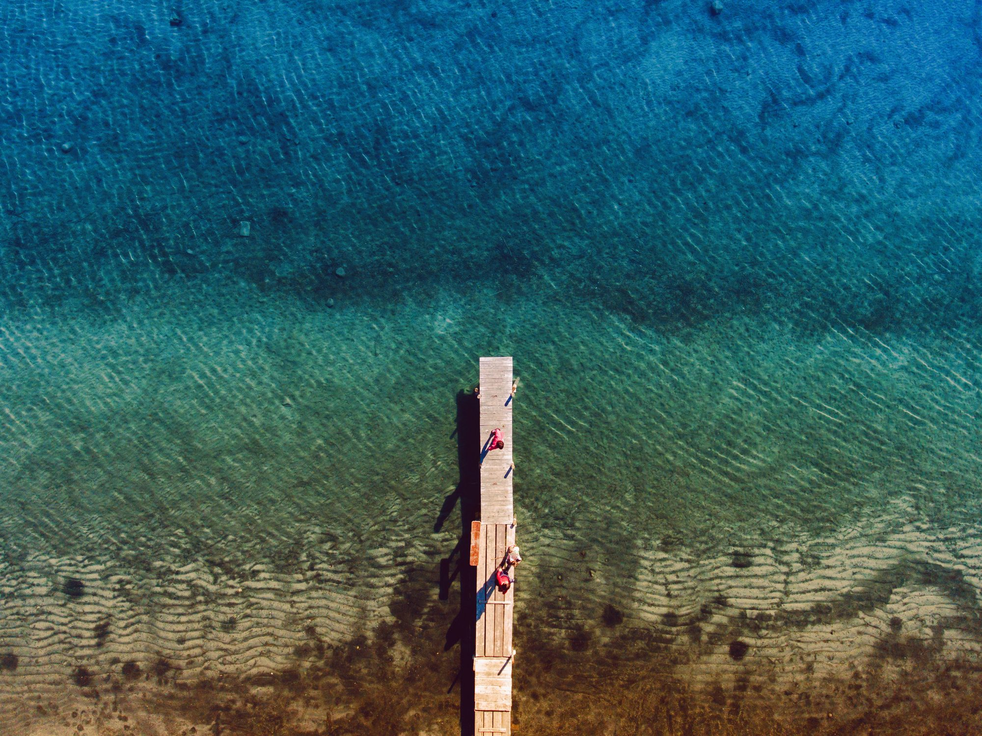 Aerial view of people standing on pier at lake