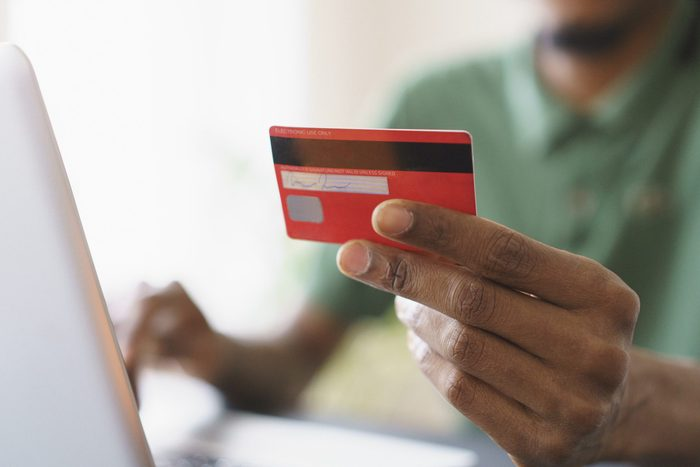 Cropped image of man holding credit while shopping online through laptop at home